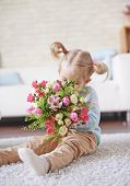 Adorable child smelling fresh flowers while sitting on the floor