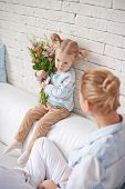 Pretty little girl with bunch of flowers sitting on sofa with her mother near by