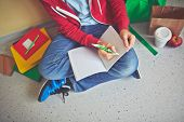 Schoolboy in casualwear making notes in exercise-book while sitting on the floor