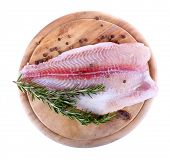 foto of pangasius  - Pangasius fillet on wooden cutting board with pepper and rosemary sprigs isolated on white - JPG