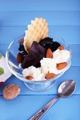 Dessert with prunes in glass bowl on color wooden table background