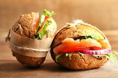 Sandwiches with salmon on wooden background