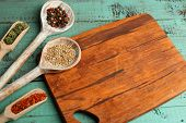 Different spices and herbs with cutting board on color wooden table background