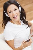 A beautiful happy girl or young woman sitting down listening to music on mp3 player and headphones