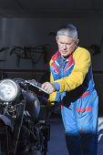 Man Pushing A Motorbike.