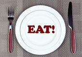 Plate with word EAT on it, fork and knife on tablecloth background