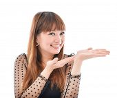 young excited woman standing happy smiling holding her hand showing something on the open palm