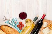 White and red wine glasses, cheese and bread on white wooden table background with copy space