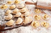 Vareniki (dumplings) with potatoes and onion. Uncooked on the wooden desk.