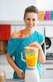 Portrait Of Happy Fitness Young Woman Making Pumpkin Smoothie In Kitchen