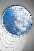 Blue Cloudy Sky Behind The Round Window With Metal Grid