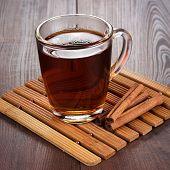 teacup with hot tea and cinnamon sticks