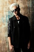 Portrait of a handsome male model with blond hair wearing black jacket and sunglasses. Urban style. Fashion.