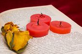 Three Red Candles And Two Dried Yellow Roses Lying On The Book