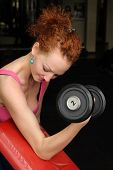 Girl with dumbbell in the gym