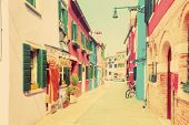 Colorful houses on Burano island, near Venice, Italy. Charming street. Vintage style, pastel colours
