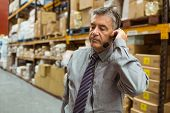 Focused manager talking in a headset in a large warehouse