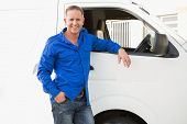 Smiling man leaning against his delivery van outside the warehouse