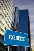 The word exercise and blue billboard against low angle view of skyscrapers