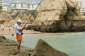 Man does fishing at Praia da Rocha beach in Portimao, Portugal.