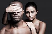 stock photo of bonding  - Beautiful Caucasian woman bonding to handsome African man and covering his eyes with hand while both standing against grey background - JPG