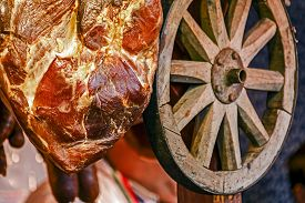 stock photo of smoked ham  - Ham smoked pork hanging and displayed for sale in a rustic atmosphere together with a wooden wheel at a traditional fair - JPG