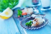stock photo of scallop shell  - scallop with caviar and lemon juice on a table - JPG