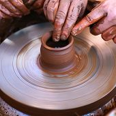 stock photo of molding clay  - Hands working with clay on pottery wheel - JPG