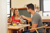 image of breakfast  - Indoor shot of young man serving coffee to his girlfriend having breakfast in kitchen at home. Smiling young couple having breakfast and looking at each other. ** Note: Shallow depth of field - JPG