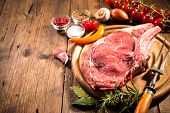 Постер, плакат: Raw fresh meat rib eye steak and seasoning on wooden background