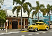 stock photo of tree lined street  - Old yellow taxi on a palm tree lined street - JPG