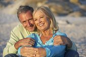 picture of couple sitting beach  - Senior Couple On Holiday Sitting On Sandy Beach - JPG
