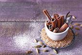 image of cinnamon sticks  - Cinnamon and vanilla sticks with sugar on wooden table background - JPG