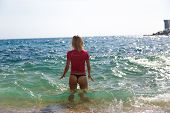 stock photo of string bikini  - Sexy girl in sportswear and tanga string gets into the sea - JPG