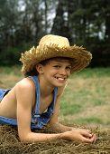 Boy On Hay Bale  Smiling