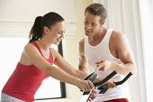 picture of exercise bike  - Young Couple On Exercise Bike - JPG