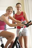 foto of exercise bike  - Young Woman On Exercise Bike With Trainer - JPG