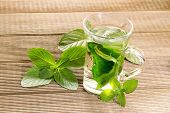 stock photo of mint leaf  - Mint tea with fresh mint leaves on a wooden background - JPG