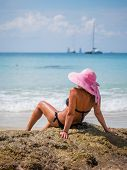 pic of beach hat  - Summer vacation woman on the beach in beach hat enjoying summer holidays looking at the ocean - JPG