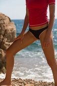 pic of string bikini  - Sexy girl in sportswear and tanga string training on the cliff of the rocky beach - JPG