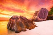 image of fiery  - Beautifully shaped granite boulders and a dramatic fiery sunset  and a white beach at Anse Source d - JPG