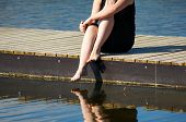 picture of jetties  - Young women sitting on the Jetty with jer legs in the lake water - JPG