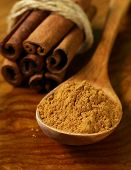 stock photo of cinnamon sticks  - fragrant cinnamon sticks and ground spices on a wooden background - JPG