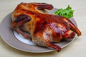 stock photo of roast duck  - Roasted duck with salad leaves on the wood background - JPG