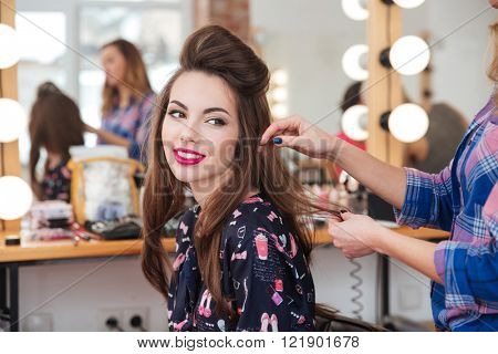 poster of Female hairdresser standing and making hairstyle to cute lovely young woman in beauty salon
