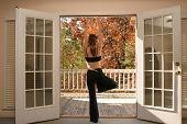 Woman Doing Yoga Looking Over Balcony