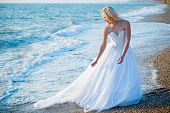 Bride in white wedding dress entering sea water at beach