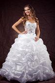 Fashion model wearing wedding dress at brown studio background