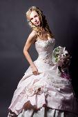 Beautiful blond bride wearing wedding dress posing on gray studio background