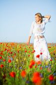 Young blond girl in flower meadow